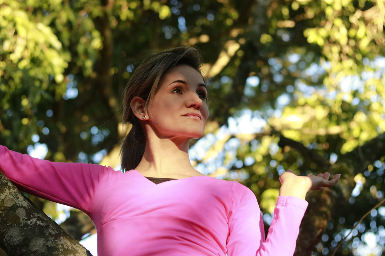 Low Angle View Of Woman Looking Away While Leaning On Tree Trunk