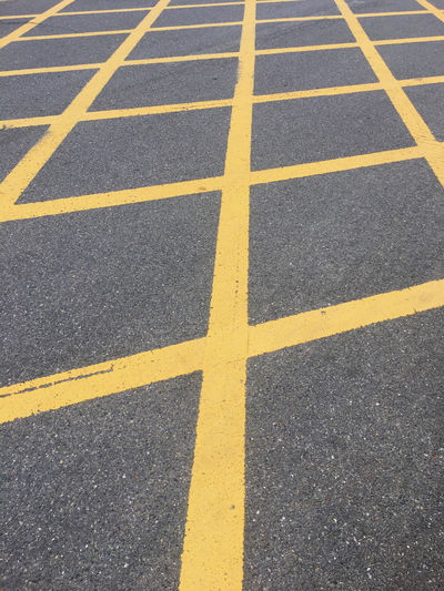 Yellow lines on the street to mark 'no-stopping area' Dividing Line Parallel Direction Street City Textured  Asphalt Pattern Sign Symbol High Angle View Marking Road Yellow Road Marking No-stopping Area