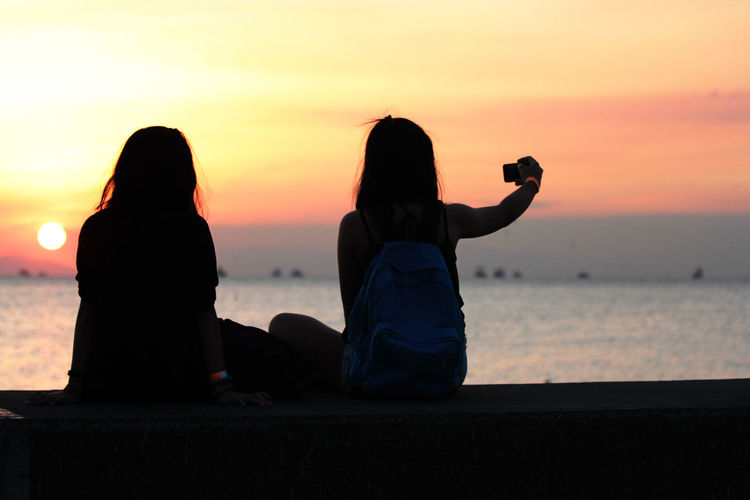 Rear view of women overlooking sea at sunset