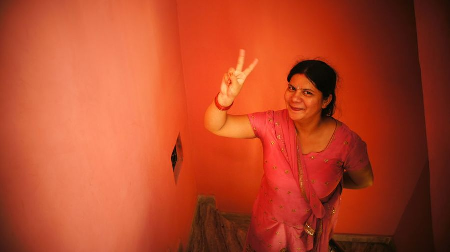High angle portrait of smiling woman gesturing peace sign at home
