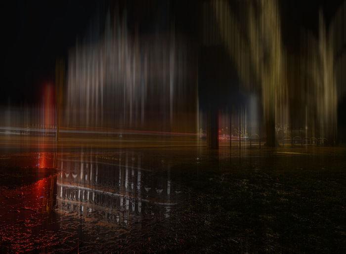 View of fountain at night during rainy season