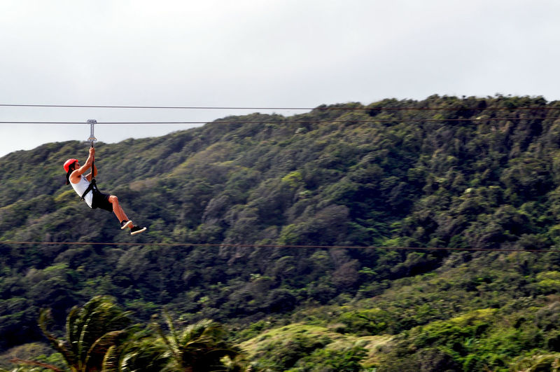 Woman Zip Lining On Mountain Against Sky