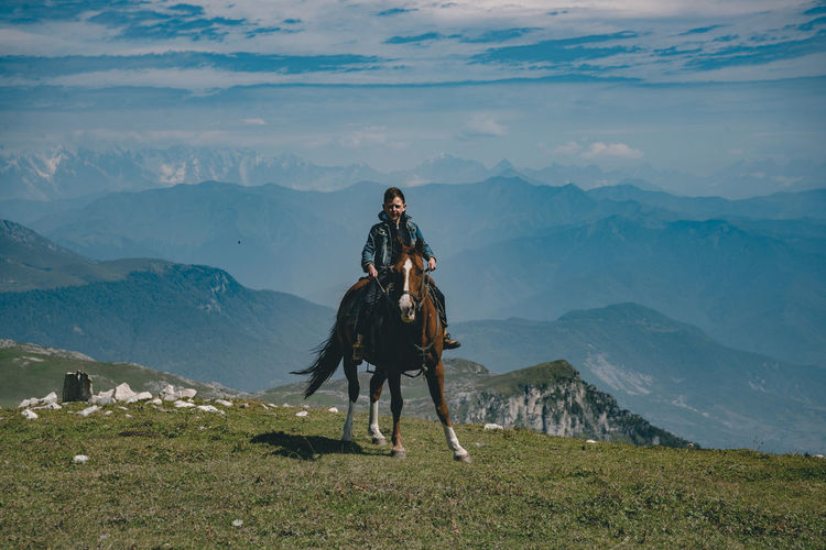 Full length of boy sitting on horse against mountain
