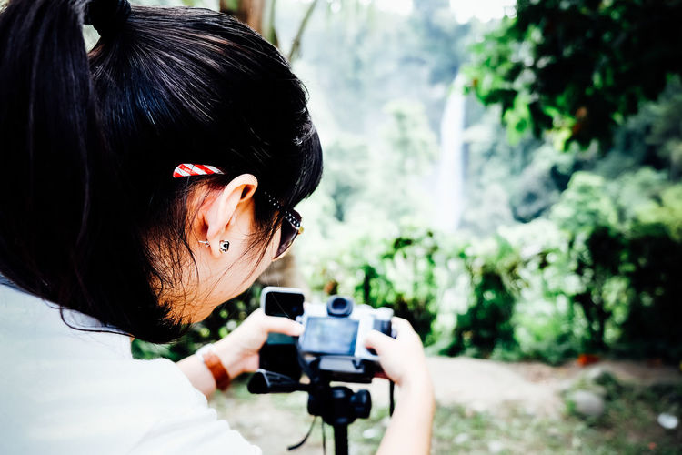 Rear view of woman photographing through slur camera at park