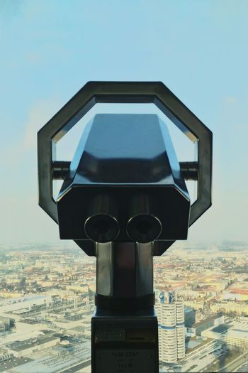 Close-Up Of Binoculars By Cityscape Against Sky