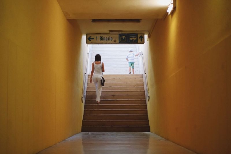 Away... Hallway Tunnel Passage Lifestyles Leisure Activity Indoors  Full Length Architecture Built Structure Stairs Train Station Family Mother And Son Motherhood Childhood Child Travel Walking Distance Standing Yellow Wall Away Woman Casual Clothing The Graphic City