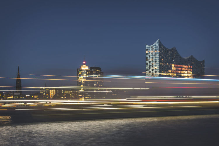 Light trails on illuminated bridge by buildings against sky at night