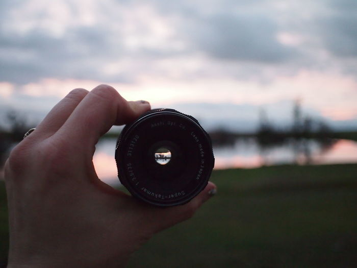 Cropped hand holding lens against cloudy sky at dusk