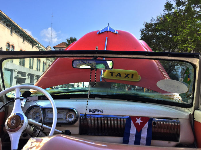Red vintage car on road against sky