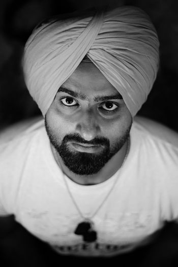 High angle portrait of young man wearing turban over black background