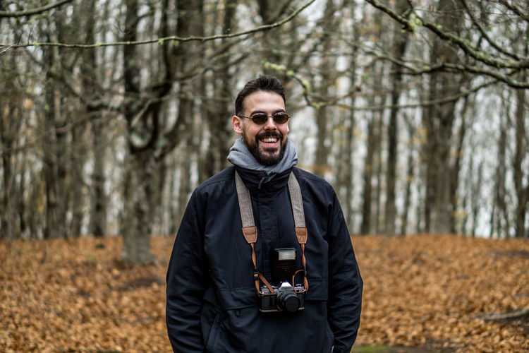 Portrait of smiling man standing in forest