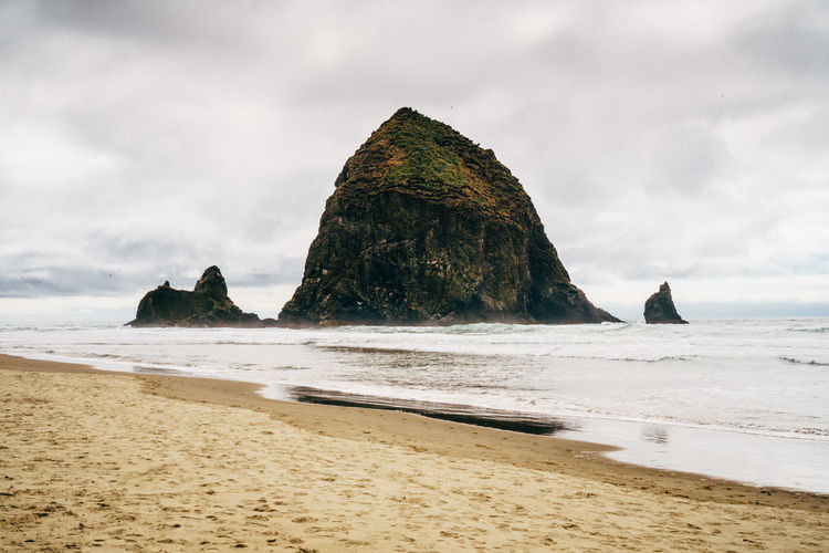Scenic View Of Cannon Beach Against Cloudy Sky