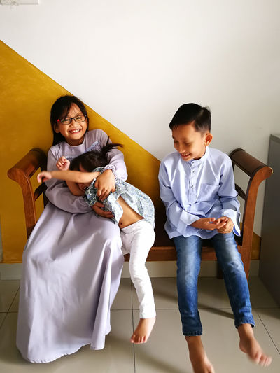 Cheerful siblings sitting on bench at home during eid-ul-fitr