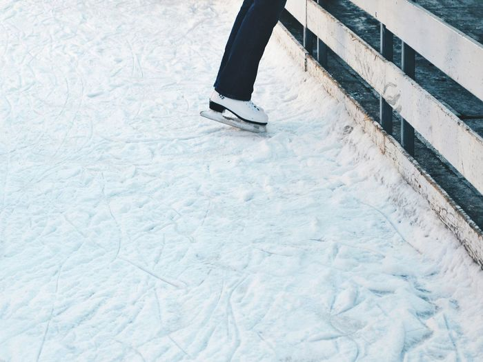Low section of person wearing ice skates standing on field