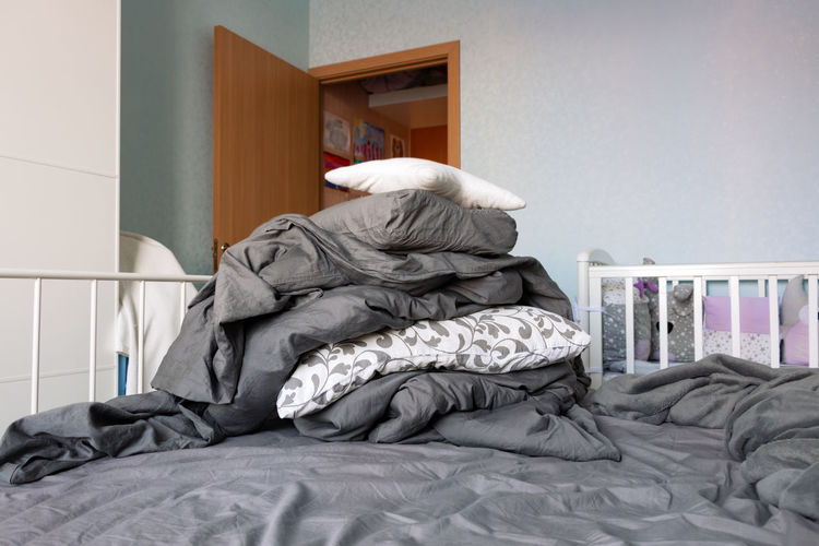 Big pile of gray linen and white pillows lies on bed in domestic room. housekeeping concept