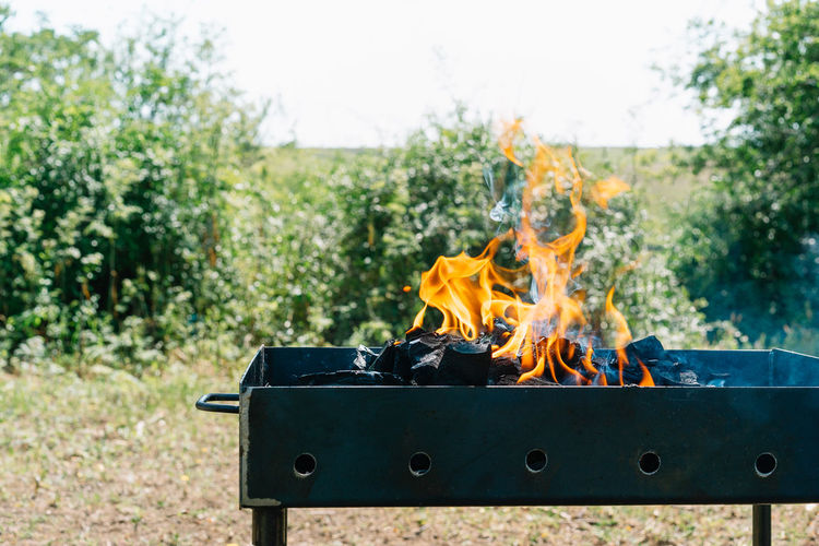 Barbecue fire on field against sky