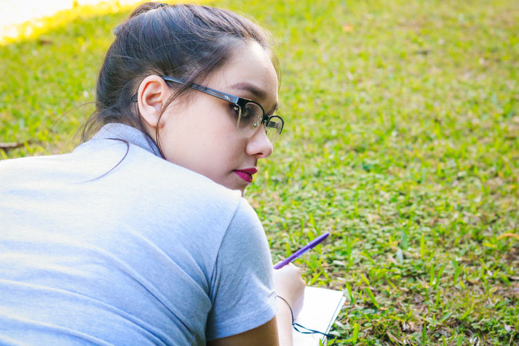 Rear view of young woman studying at park