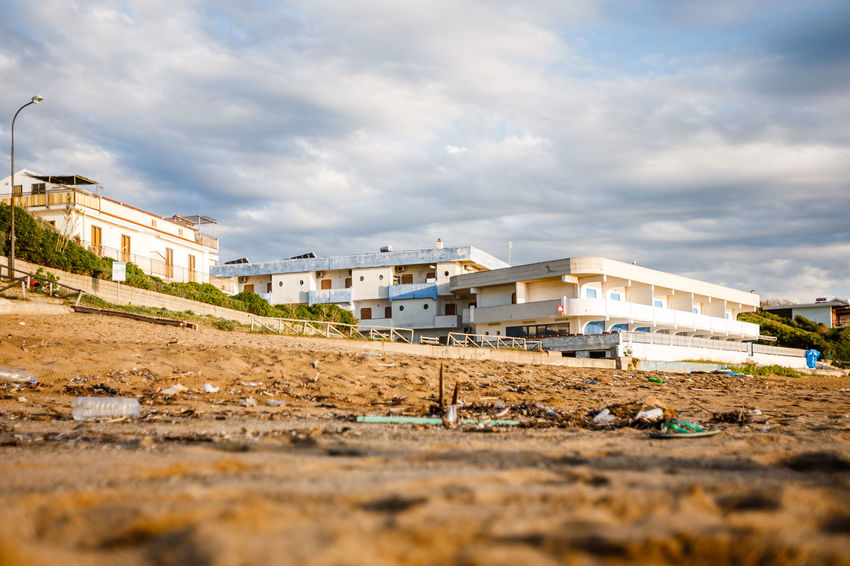 plastic garbage on the beach Abandoned Architecture Building Building Exterior Built Structure Cloud Cloud - Sky Cloudy Day Environment Protection Environmental Conservation Field Garbage House No People Outdoors Overcast Plastic Garbage Pollution Residential Building Residential Structure Selective Focus Sky Surface Level Weather
