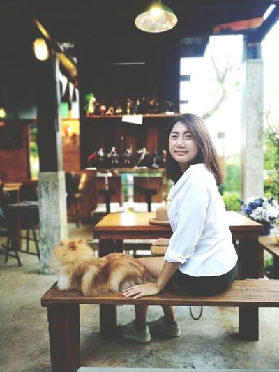 Portrait of smiling woman with dog sitting on table in cafe