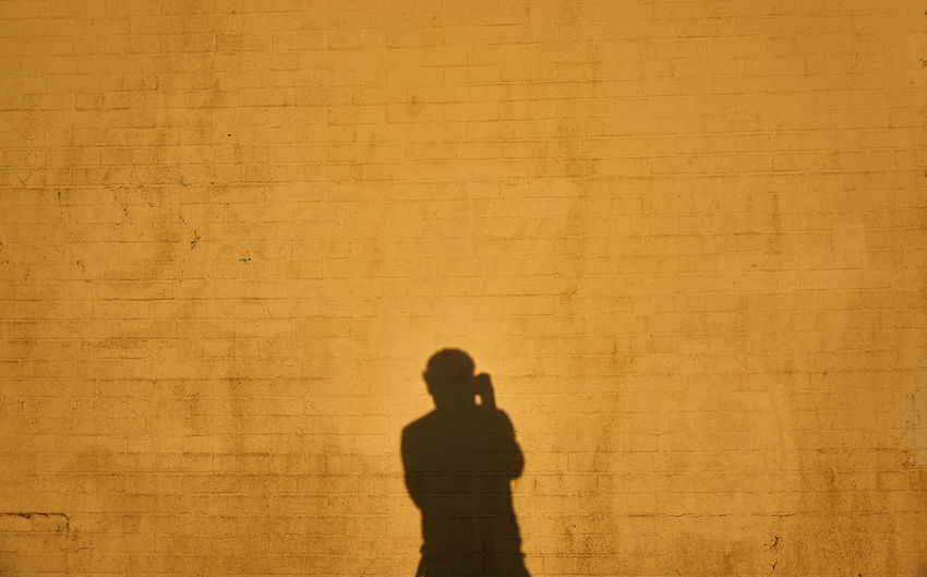 Shadow of man on brown wall during sunny day