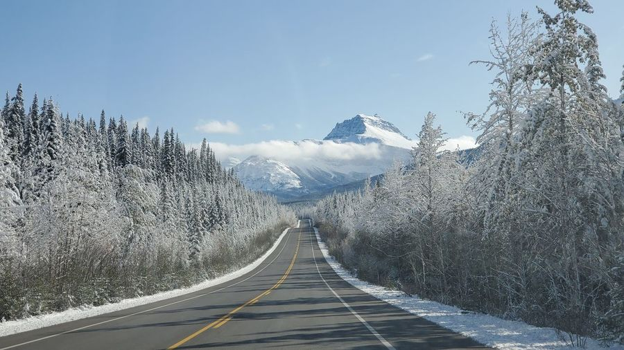 Empty road amidst snow covered mountains against sky