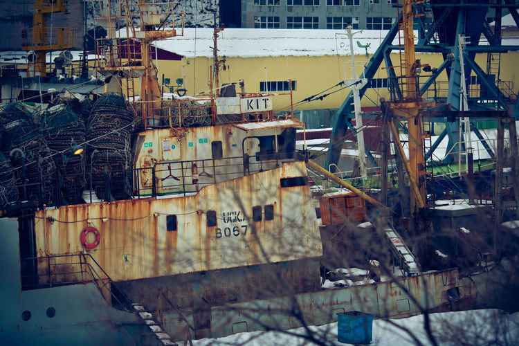 Sailboats moored at construction site against buildings