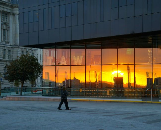 Silhouette man standing by glass building in city during sunset