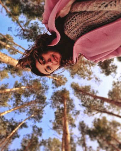 Low angle view portrait of girl against trees
