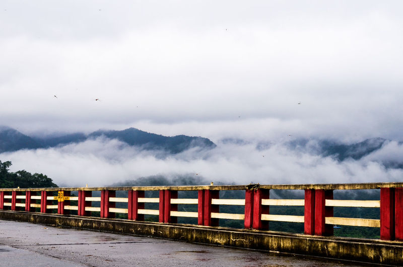 View Of Bridge Against Foggy Mountains