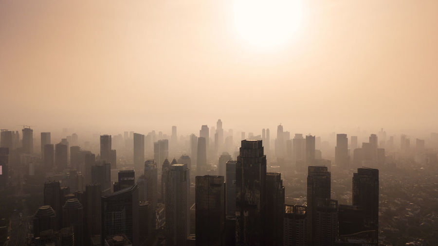 City Architecture Skyscraper Cityscape Building Building Exterior Built Structure Office Building Exterior Sky Landscape Urban Skyline Nature City Life Fog Sunset No People Residential District Sun Tall - High Smog Outdoors Modern Financial District  Pollution