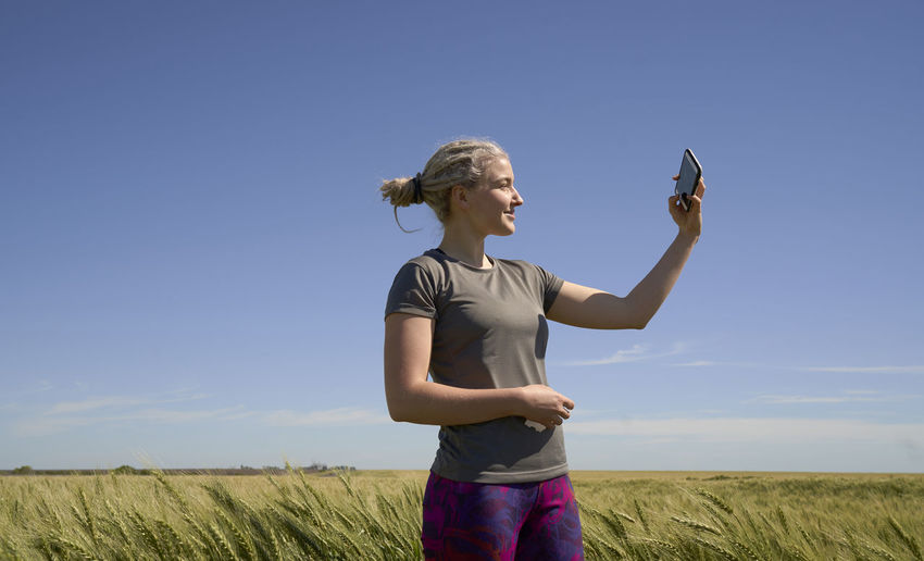 Full length of woman holding mobile phone while standing on field