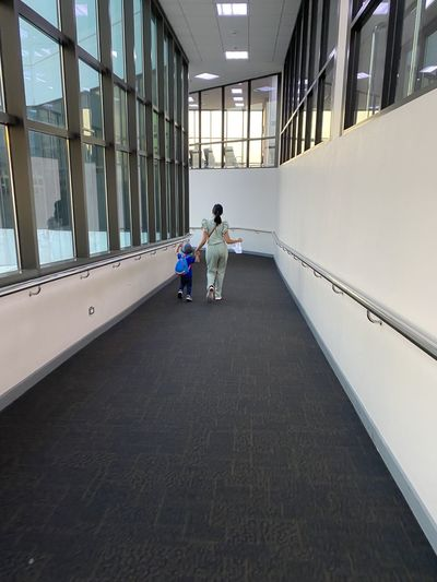 Rear view of women walking in corridor of building