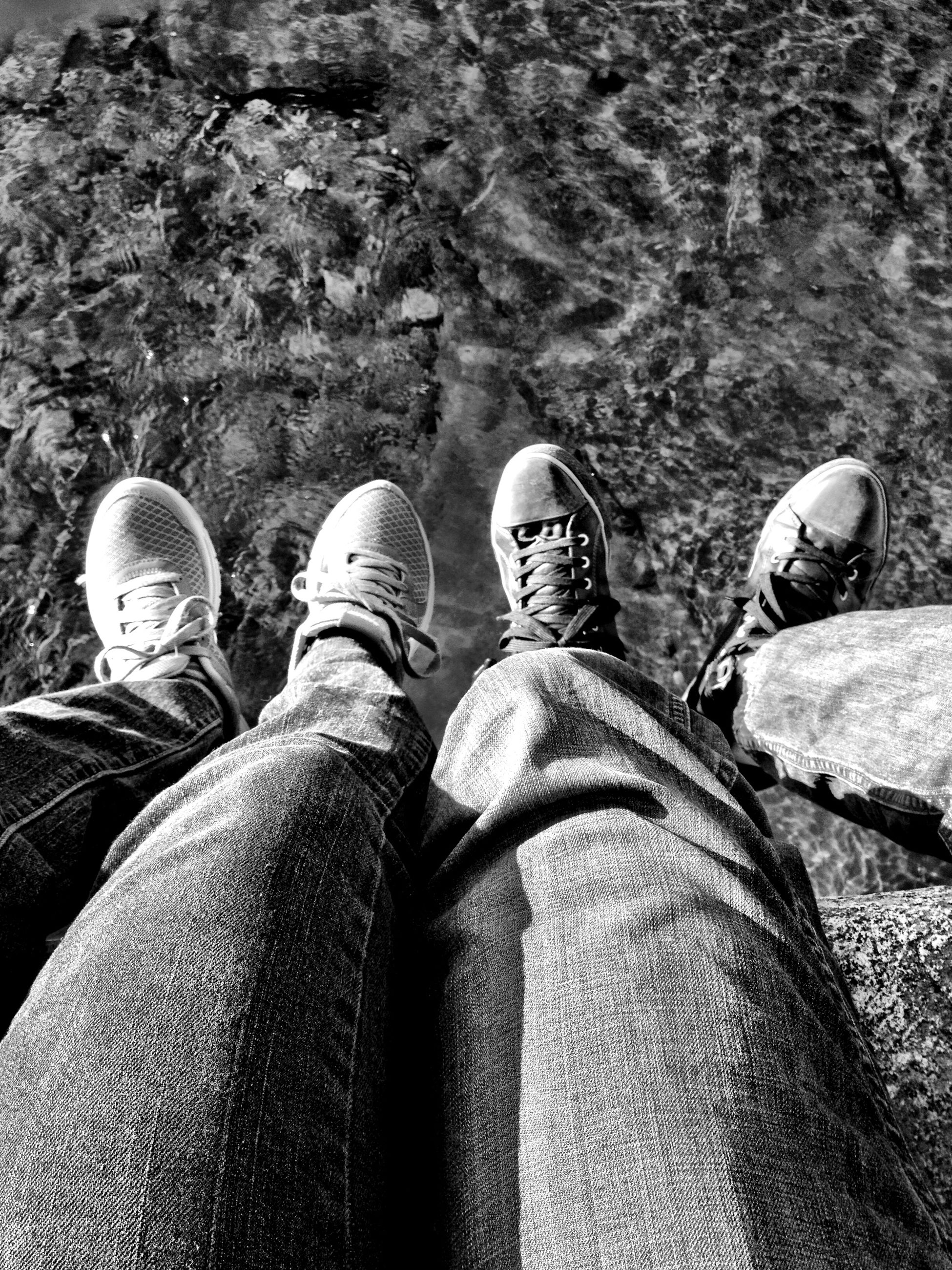 low section, person, shoe, personal perspective, lifestyles, men, human foot, leisure activity, jeans, high angle view, standing, relaxation, unrecognizable person, footwear, resting, outdoors, day