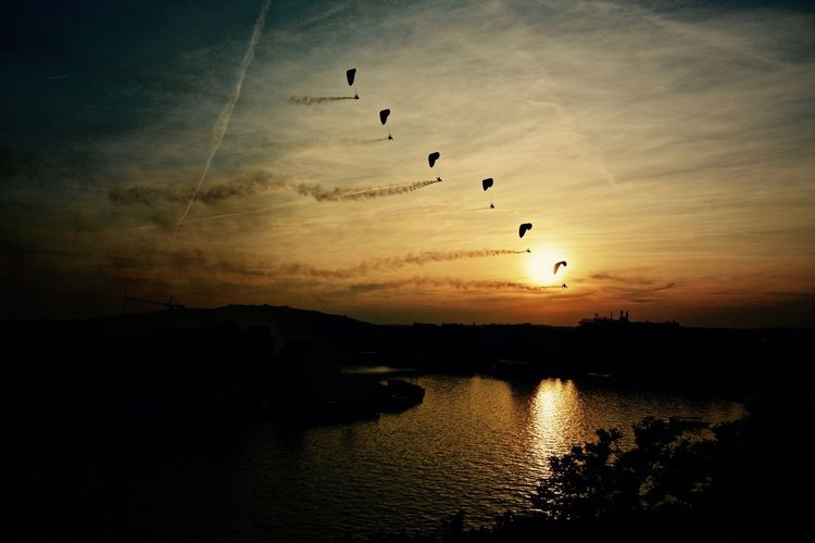 Silhouette of hot air balloons against sky during sunset