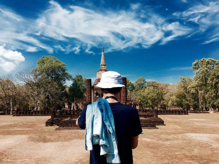 Rear view of man standing by wat chong lom at sukhothai historical park