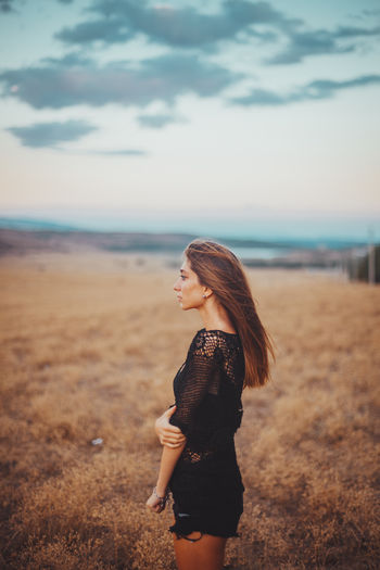 Thoughtful woman standing on field against sky