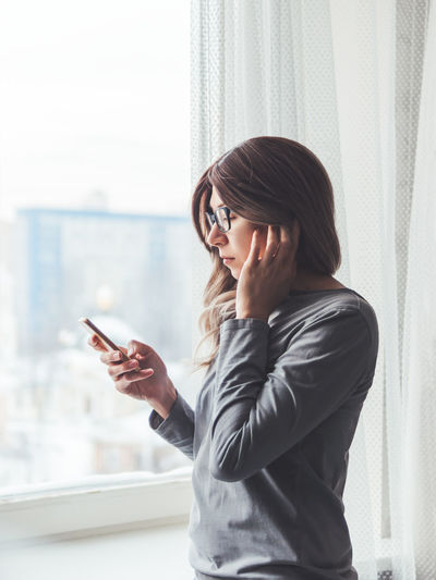 Thoughtful woman with eyeglasses looks at smartphone. online media. wireless headphones under hair.