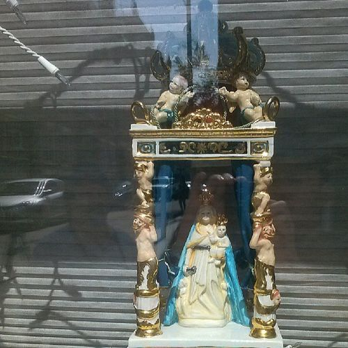 A miniature of the larger statue in a window. A most curious and charming discovery :)