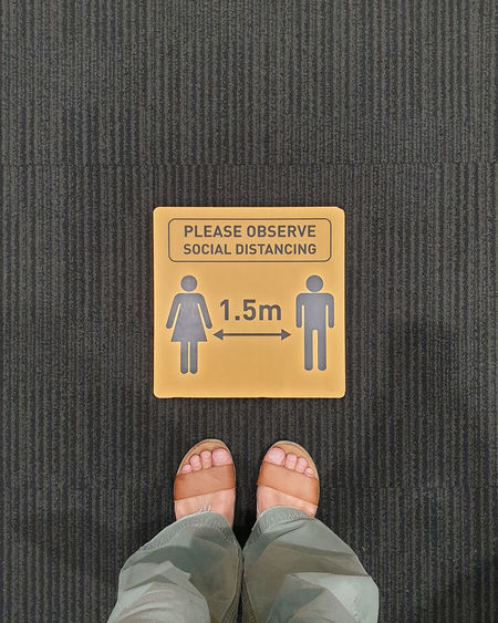 Low section of person standing on yellow sign