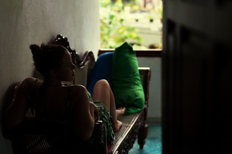 Rear view of woman relaxing on sofa at home