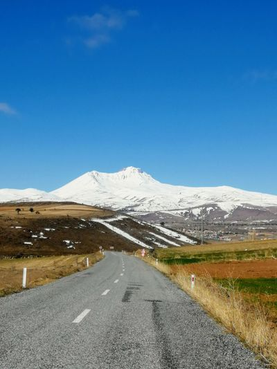 Road leading towards snowcapped mountain against blue sky