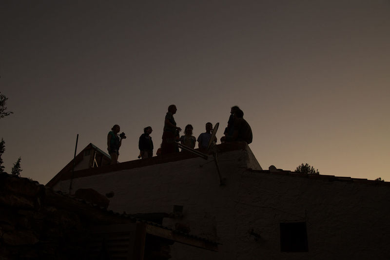 Low angle view of people on roof against clear sky