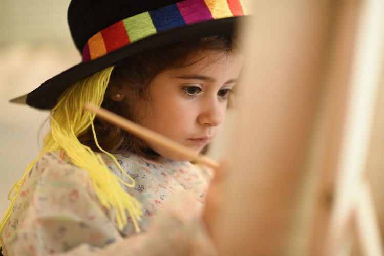 Happy little girl painting a picture at home Childhood Child Portrait Headshot Females One Person Selective Focus Girls Offspring Looking Innocence Women Hat Clothing Hair Cute Looking Away Close-up Contemplation Hairstyle Floral Pattern