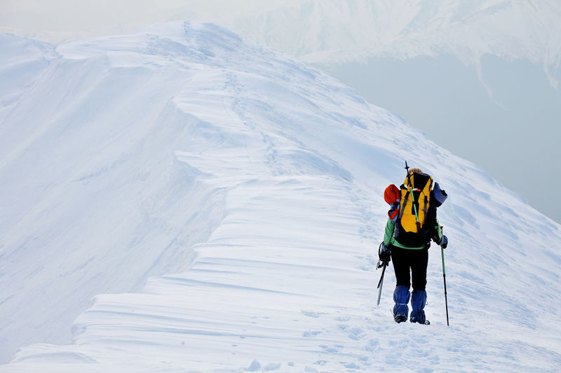 Rear view of person climbing mountain in winter