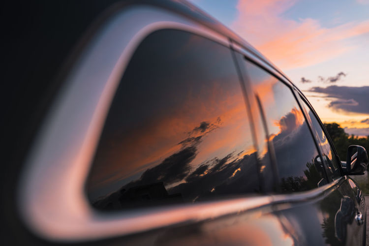 Close-up of side-view mirror against sky during sunset