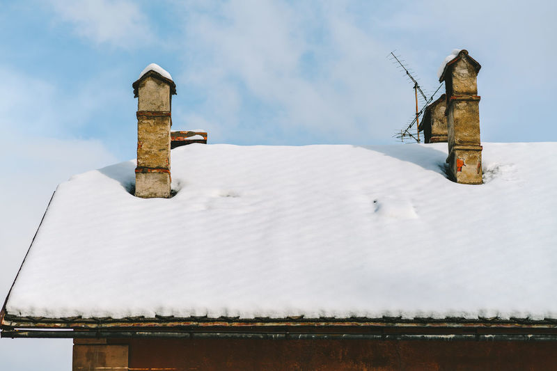 Snow covered roof against sky