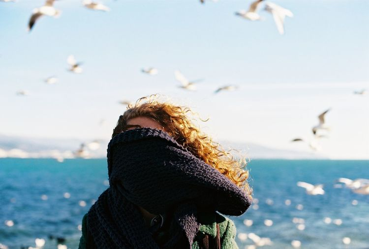 Close-up of woman with face covered by shawl against sea
