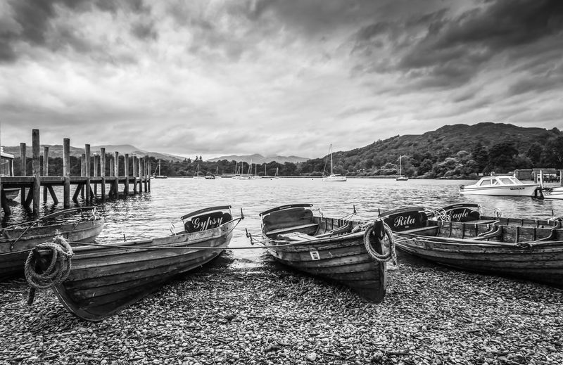 Wooden boats at Ambleside Pier on the shores of Lake Windermere, England. Boats Wooden Boats Overcast Lake Windermere Cumbria England Uk Ambleside Pier Jetty Fishing Boats Oars Nautical Vessel Moored Nature Landscape Hills Water Lake Lakeside Monochrome Black And White Photography Clouds Sky