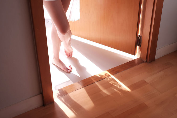 Low section of sensuous woman standing in doorway at home