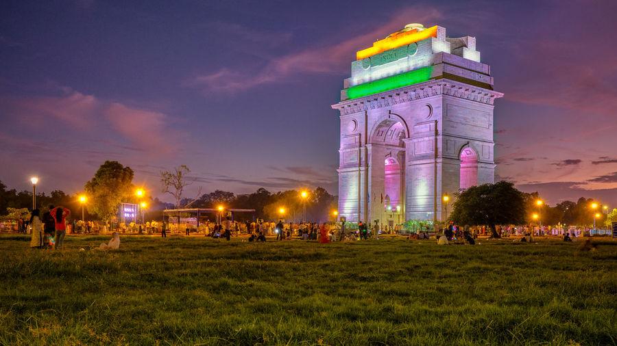 Crowd at illuminated park against sky at night